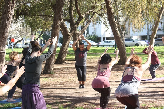 Eddy Toyonaga leading a yoga class in the park for the Acro yoga community