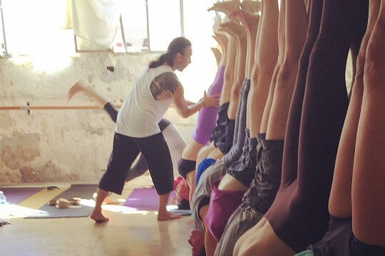 Eddy Toyonaga correcting students in a group arm balance yoga workshop