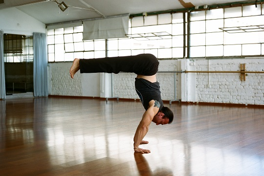 Eddy Toyonaga in handstand pike pose in Naim Studio Tel Aviv