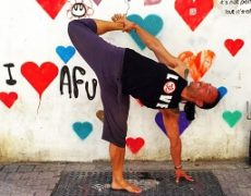 Eddy Toyonaga performing a yoga pose in Tel Aviv in front of graffiti