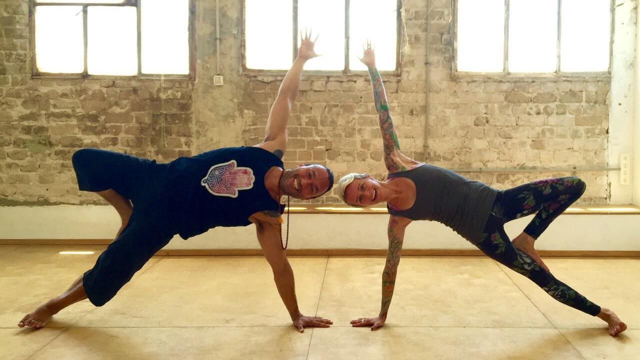 Eddy Toyonaga and Jackie displaying yoga poses for the Yoga Arava festival 2016