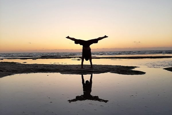 Eddy Toyonaga doing a handstand at the beach in sunset